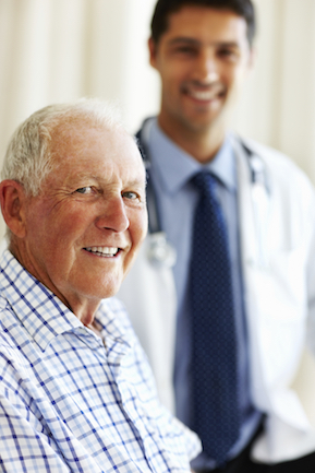 Elderly patient in the fore-ground smiling with the doctor in the background